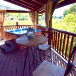 Upper porch, partially covered, with hot tub  Front Porch - covered with rockers. at Tahlequah Cabin, Arbors Vacation Rentals - Pigeon Forge
